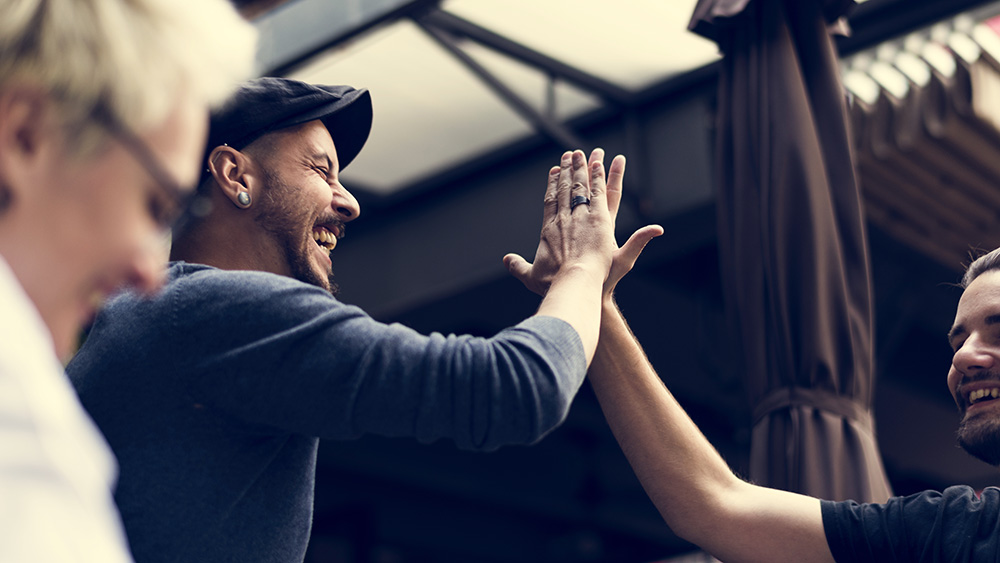 Two employees high-five.