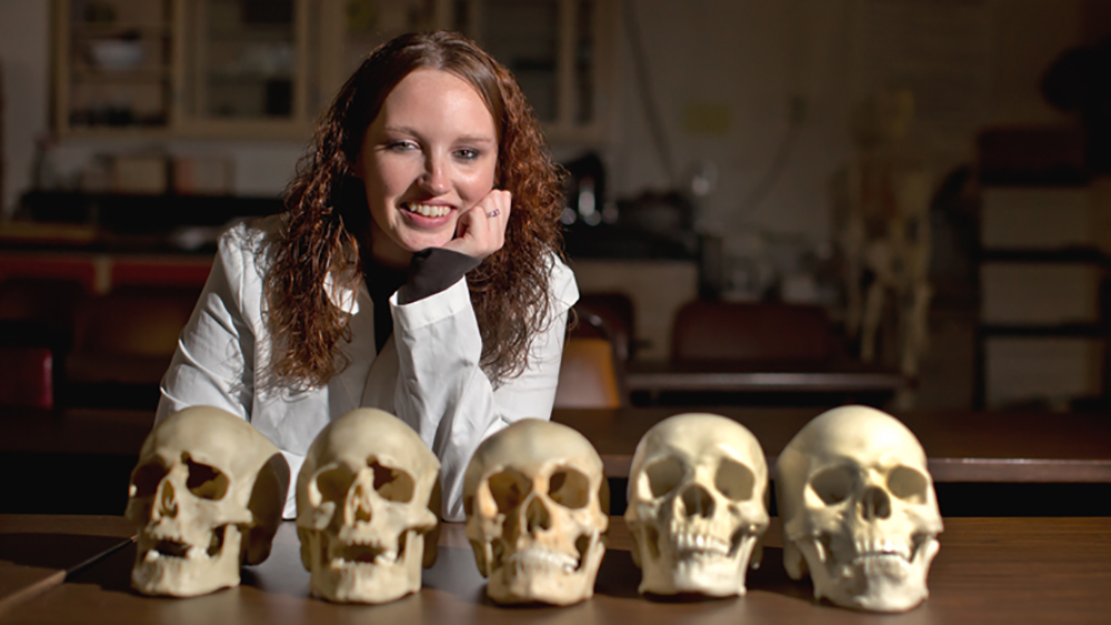 An anthropology students poses with human skulls.