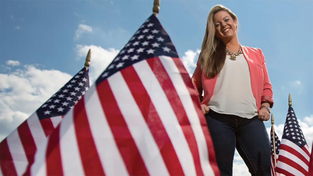 A Cal U student poses with American flags.