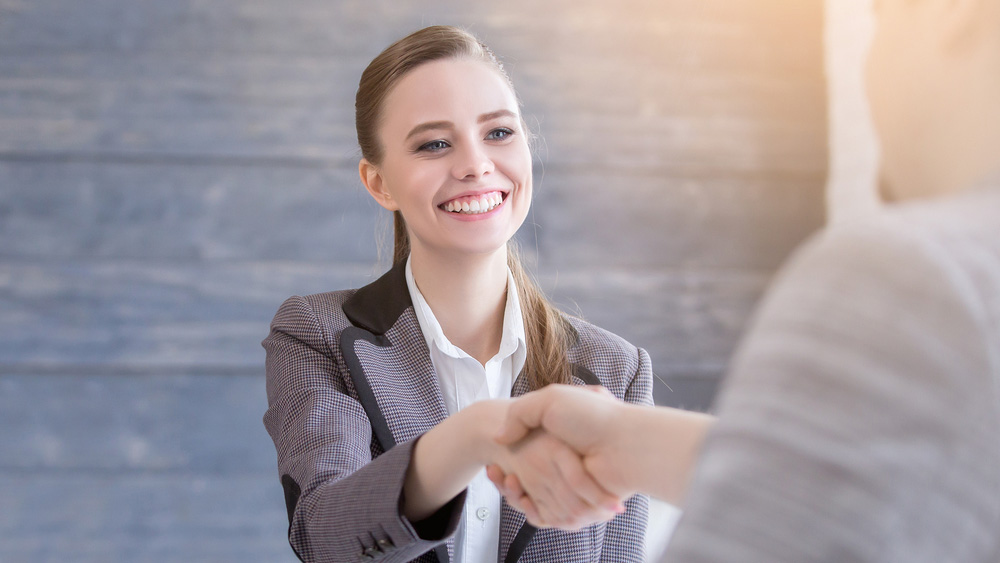 A female student shakes hands during an interview.