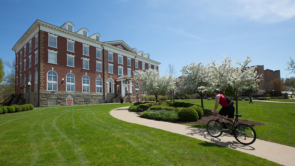 A Cal U student riding his bike on a beautful day at campus.